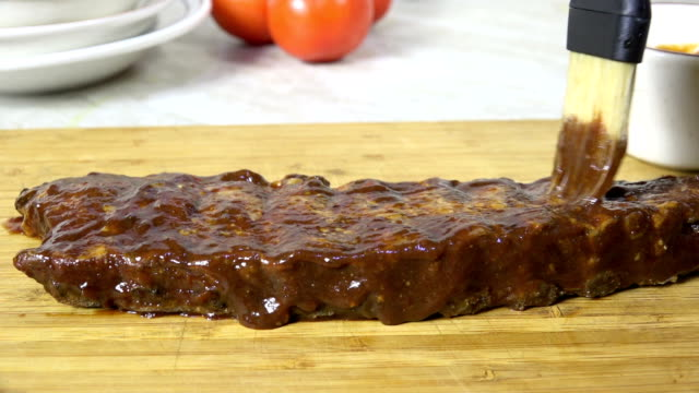 Brushing sauce on fresh barbecued ribs Brushing barbecue sauce on ribs closeup sauce stock videos & royalty-free footage