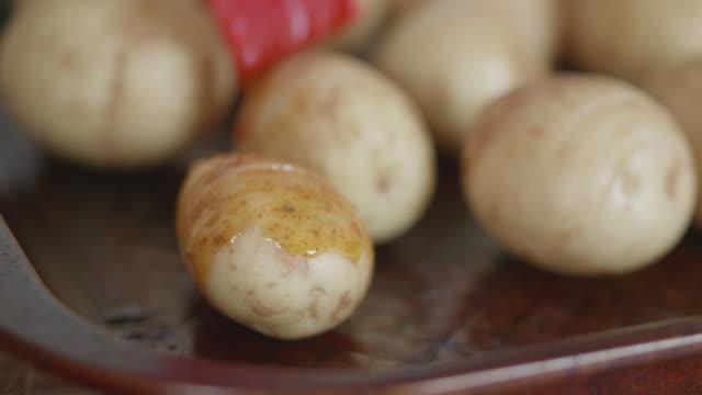 brushing spicy oil on hasselback potatoes - молодой картофель стоковые видео и кадры b-roll