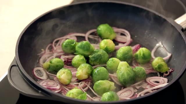 brüssel rosenkohl mit zwiebeln auf die frying pan - bio lebensmittel stock-videos und b-roll-filmmaterial