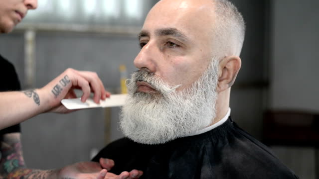 vidéos et rushes de barber clipper mows barbu brutal adulte senior bas - salons et coiffeurs