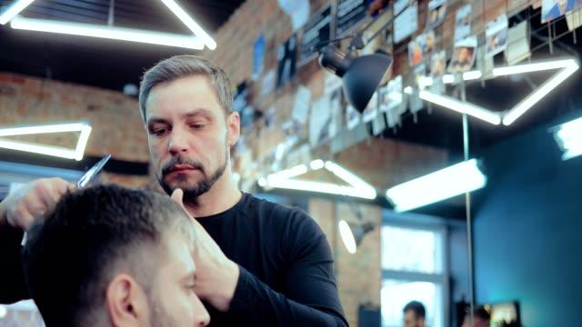 vidéos et rushes de le barbier brutal coupe le bang d'un homme dans un salon de coiffure. vue portrait. - coiffeur