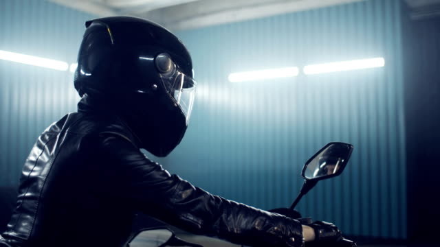 Brutal biker girl. Stylish brutal biker girl in a black glossy helmet and black leather jacket is sitting on his bike. Neon illumination. Cooking in the night races. Moto service. Frame for the film. crash helmet stock videos & royalty-free footage