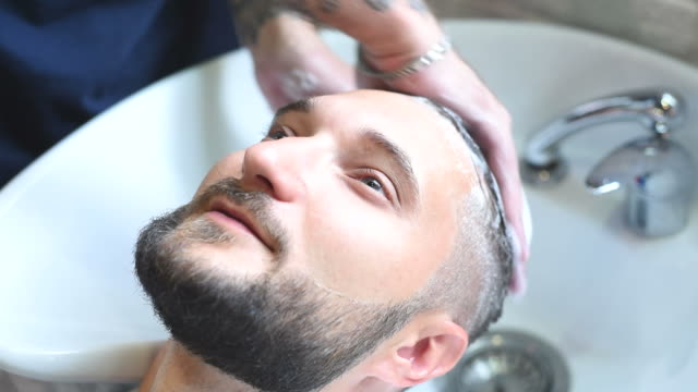 brutal hairdresser washes head of a bearded hipster video