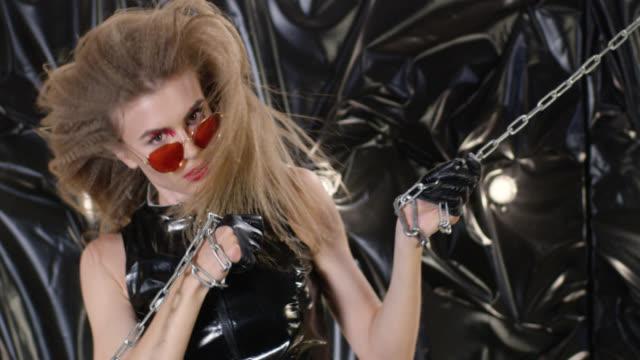 金属チェーンでキャプチャされた残忍なの探しているファッション性の高いモデルは。ファッションのビデオ。 - グリースペイント点の映像素材/bロール