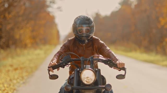 vídeos de stock e filmes b-roll de brutal man in glasses and a helmet rides on the highway on a motorcycle. golden autumn. - helmet motorbike