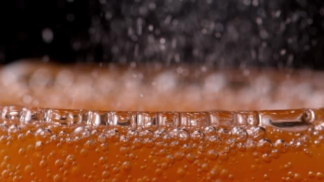 Bubbling orange soda drink fizzing in glass - Close up