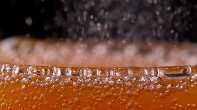Bubbling orange soda drink fizzing in glass - Close up sparkling orange juice soda drink seen from the rim of the glass. carbonated stock videos & royalty-free footage