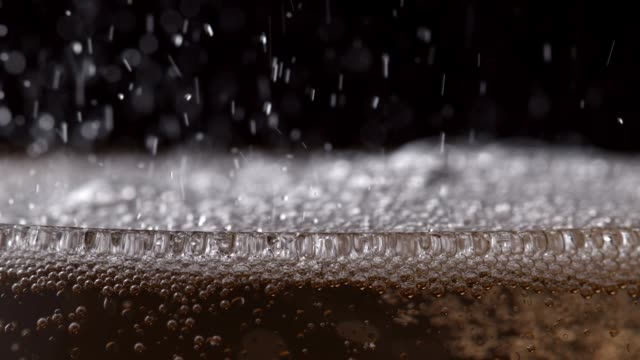 Bubbly drink fizzing in glass Close up