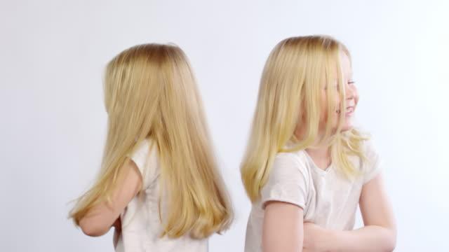 sprudelige zwillings-girls, die zum streit vorgeben - rücken an rücken stock-videos und b-roll-filmmaterial