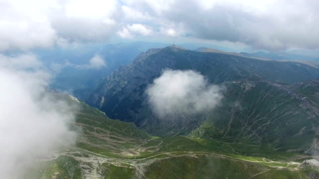 Bucegi mountains, Romania, aerial flight from the first layer of clouds video
