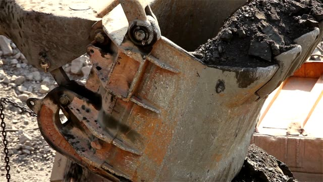Bucket of an industrial excavator close-up. Excavator loads the raw materials in the dumper, work in the iron ore quarry. video