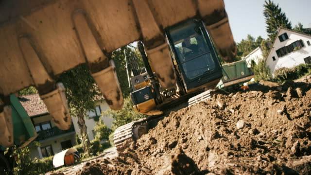 SLO MO Bucket on the excavator digging into the soil at the building site in sunshine
