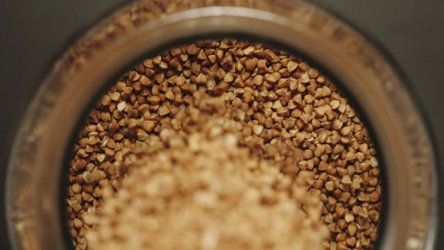 vídeos de stock, filmes e b-roll de vista superior: grões do trigo mourisco que derramam em um frasco de vidro-slow motion - punhado