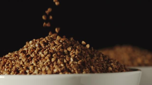 slow motion: bovete korn hälla i en vit skål-närbild - fiber bildbanksvideor och videomaterial från bakom kulisserna