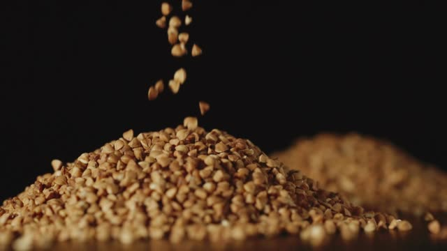 slow motion: buckwheat grains pouring on a table - close up - mucchio video stock e b–roll