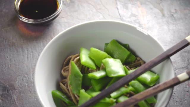 vídeos de stock, filmes e b-roll de macarrão de trigo sarraceno com feijão verde em uma tigela de cerâmica e varas - comida salgada