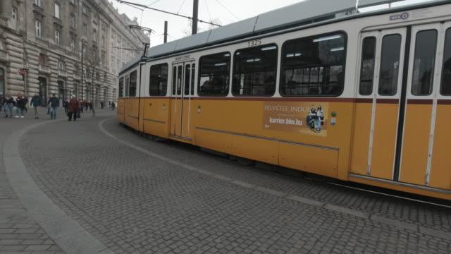 vista esterna del parlamento di budapest con tram che passa di 2 - ungheria video stock e b–roll