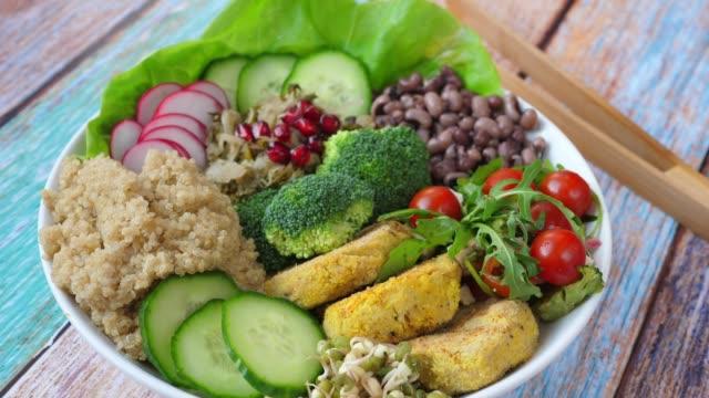 キヌア、ひよこ豆ファラフェルパティ、赤豆とサラダとブッダボウル。ヘルシービーガンフードコンセプト - ベジタリアン料理点の映像素材/bロール