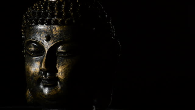 buddha face, deity buddhist, rotating at black background justify at left - buddha video stock e b–roll