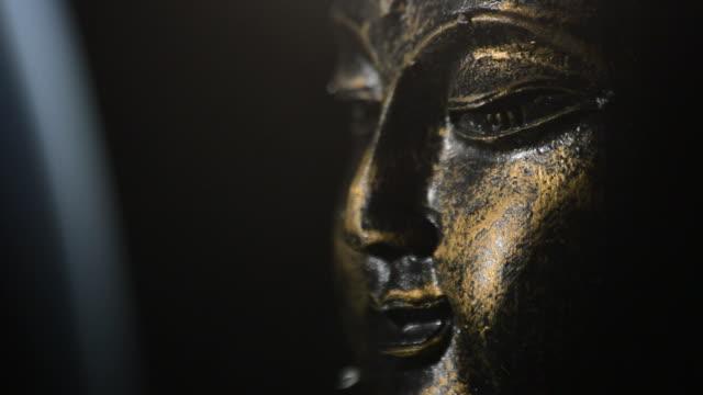 Buddha face, figure buddhist, rotating at black background with smoke video