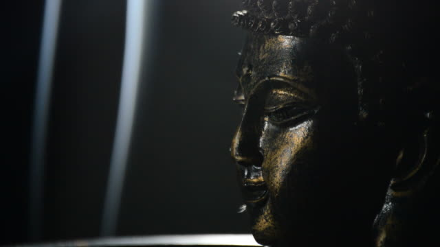 buddha face, god buddhist, rotating at black background justify at right - buddha video stock e b–roll