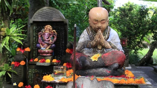 Buddha statue and fragrant wand in tropical garden. Bali, Indonesia Buddha statue and fragrant wand in the tropical garden in Ubud, island Bali, Indonesia, close up buddha stock videos & royalty-free footage