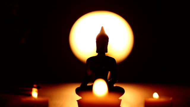 Buddha statue and three candles with lot incense smoke video