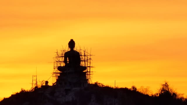 Buddha statue on mountain at sunset. video