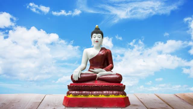 статуя будды на деревянный пол, время перерыва облака двигаться фоне - верующий стоковые видео и кадры b-roll