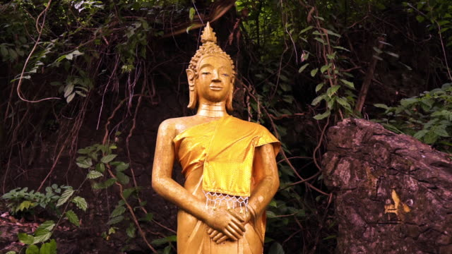 buddha statue standing with hands clasped, mount phousi, luang prabang, laos, zoom in - mudra video stock e b–roll