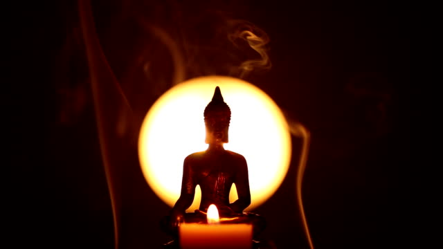Buddha statue with candle and hand lighting up incense video