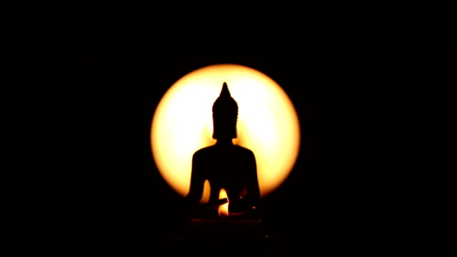 Buddha statue with focus on the candles video