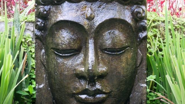 buddha with falling water in the tropical garden in ubud, bali. - buddha video stock e b–roll