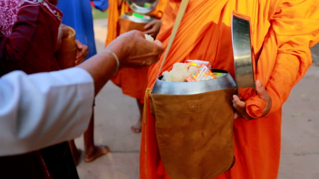 Buddhist give food offerings to a Buddhist monk in morning video