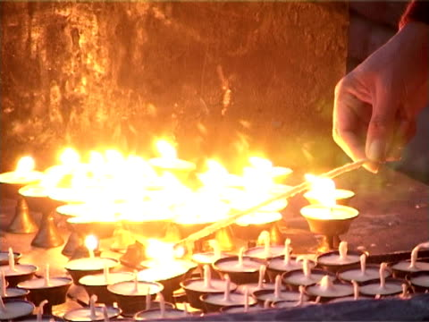 Buddhist monk lights butter lamps (candles). video