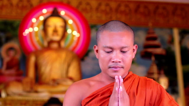 Buddhist monk with orange robe pray in temple video