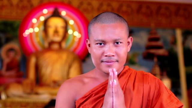 vídeos y material grabado en eventos de stock de monje budista con orar en el templo naranja, bata de baño - hermano