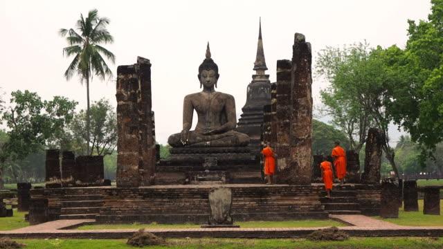 Buddhist Monks at Wat Mahathat Temple, Sukhothai Historical Park, Thailand video