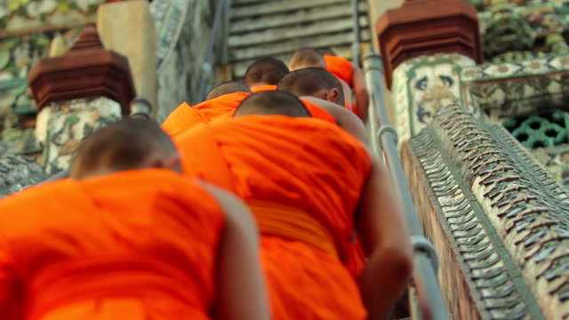 Buddhist monks walking up steep stairs at a temple video