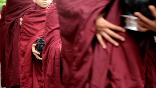Buddhist novices walk to collect alms and offerings in Mandalay, Myanmar Buddhist novices walk to collect alms and offerings in Mandalay, Myanmar bagan stock videos & royalty-free footage