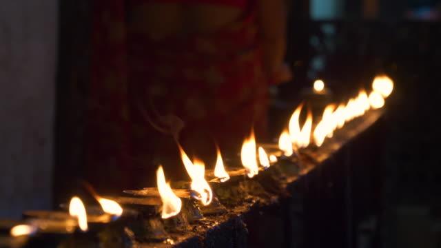 yakin: budist uygulayıcılar bir tapınağın içinde küçük yağ mumları yakıyorlar. - stupa stok videoları ve detay görüntü çekimi