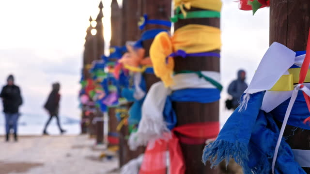 vídeos de stock e filmes b-roll de buddhist ritual poles with colored ribbons in the winter at the holy site of lake baikal. sacred place. wooden poles with a lot of imposed multicolored flaps and ribbons made of fabric. - irkutsk