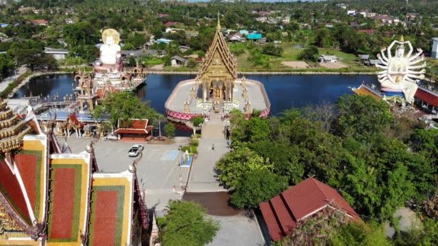 湖の近くの仏教寺院。サムイ島の晴れた日に湖の近くに位置する素晴らしい仏教寺院の屋根や彫像のドローントップビュー。ワット・プライ・レムと笑顔の仏とグアン・イン - サムイ島点の映像素材/bロール