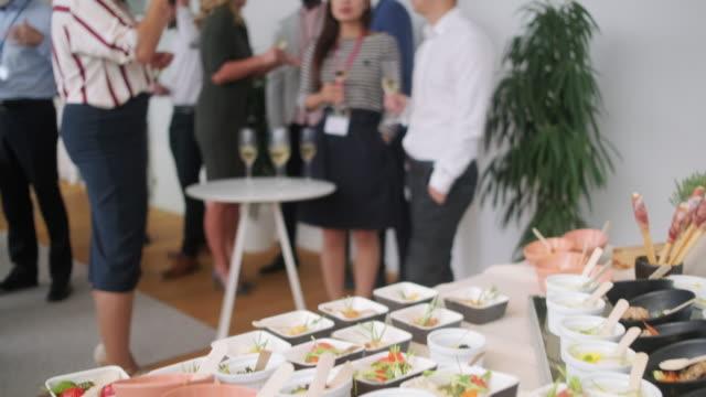 vídeos de stock, filmes e b-roll de buffet de pequenos pratos e colegas desfrutando de festa de escritório - festas no escritório