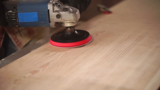 buffing works by wood in a workshop, close-up of electro grinder - levigatrice video stock e b–roll