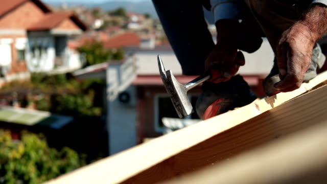 builder at work with wooden roof construction