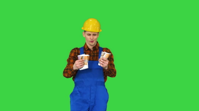 Builder counting his salary and dancing in a comic way on a Green Screen, Chroma Key