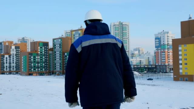 ingegnere costruttore che cammina verso il cantiere - dorso umano video stock e b–roll