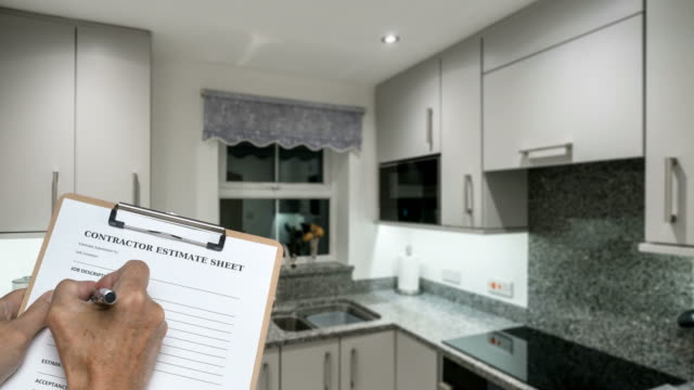 vídeos de stock e filmes b-roll de builder fills out estimate for decorating small compact modern kitchen - obras em casa janelas