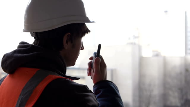 A builder from a high-rise building coordinates work using a walkie-talkie video